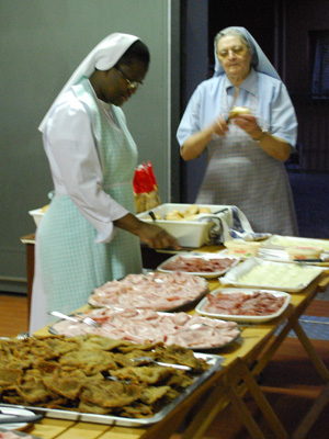 Sr. Myriam Kasaila and Sr. Leonida Deretti prepare provisions for the bag lunches of the Chapter participants who depart for the spiritual exercises in Mornese.
