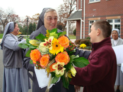 "New Jersey. Visit of M. Yvonne Reungoat to the province ""St. Philip the Apostle"" (SUA). A student presents flowers to Mother."