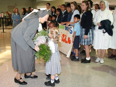 "Louisiana. Visit of M. Yvonne Reungoat to the province ""St. Philip the Apostle"" (SUA). Two girls present flowers to M. Yvonne."