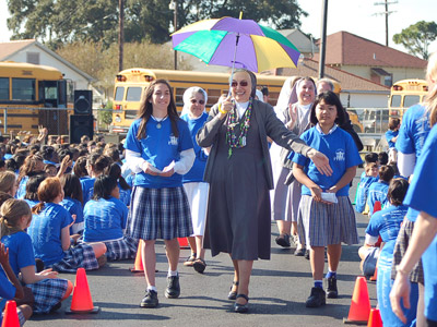 "Louisiana. Visit of M. Yvonne Reungoat to the province ""St. Philip the Apostle"" (SUA). Arrival of M. Yvonne to Immaculate Conception School (Marrero) with and umbrella and necklaces sporting the Mardi Gras colors."