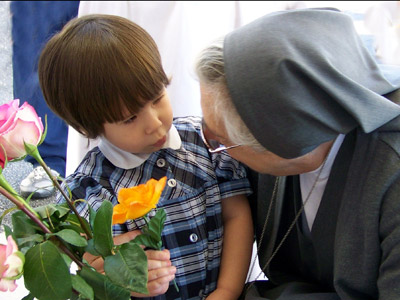 "Texas. Visit of M. Yvonne Reungoat to the province ""Mary Immaculate"" (SUO). Catherine McCollum, student of St. John Bosco School (Austin) has a tender moment with M. Yvonne."