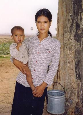 A young woman with her child goes to collect water.