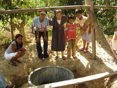 Drilling wells to provide drinking water for a group of poor families( Sr. Maria Y. and volunteers THA)